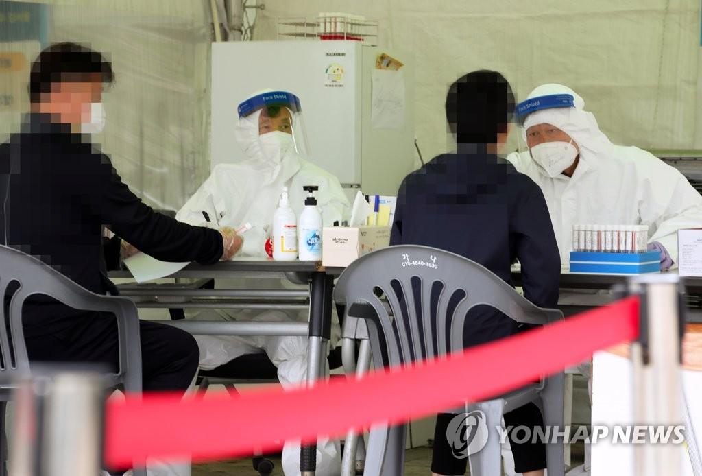 4月6日,在设于光州广域市政府广场的临时筛查诊所,市民们接受新冠病毒检测。 韩联社