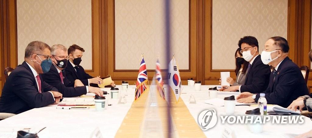 4月6日,在中央政府首尔办公楼,韩国副总理兼企划财政部长官洪楠基(右一)会见《联合国气候变化框架公约》缔约方第26次会议(COP26)主席阿洛克·夏尔马(左一)。 韩联社/企划财政部供图(图片严禁转载复制)