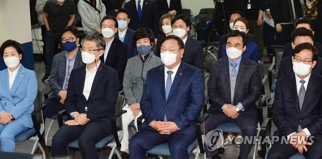 4月7日,在位于首尔汝矣岛的执政党共同民主党办公楼,该党党鞭兼代理党首金太年(前排左三)观看三大电视台出口民调结果。 韩联社