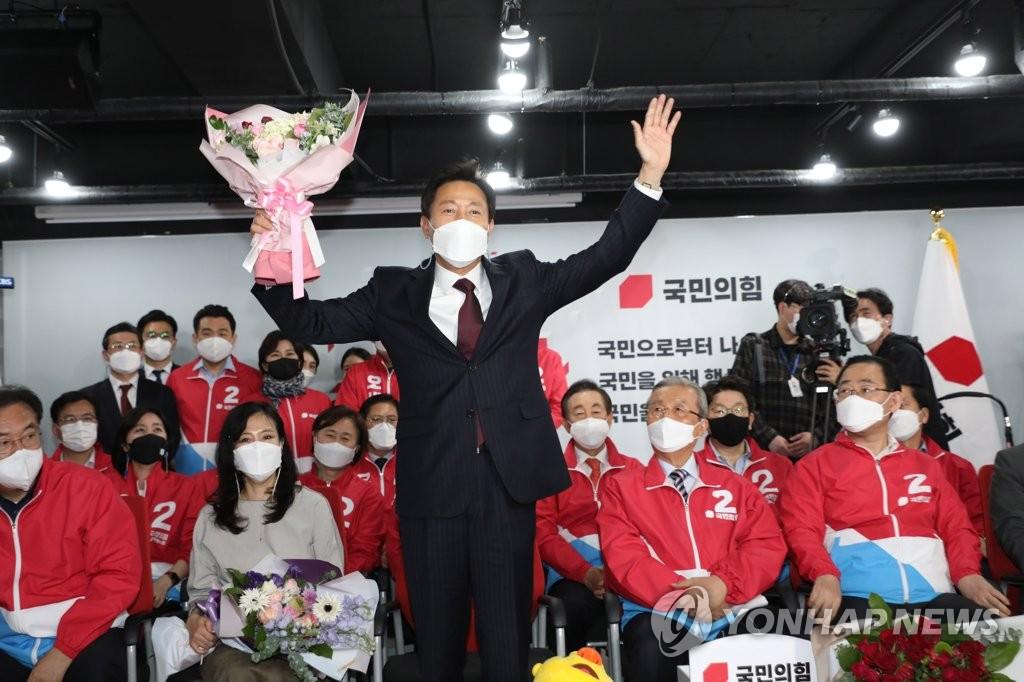 4月8日,在位于首尔汝矣岛的最大在野党国民力量办公楼,首尔市长补选国民力量候选人吴世勋手举起花束庆祝。 韩联社