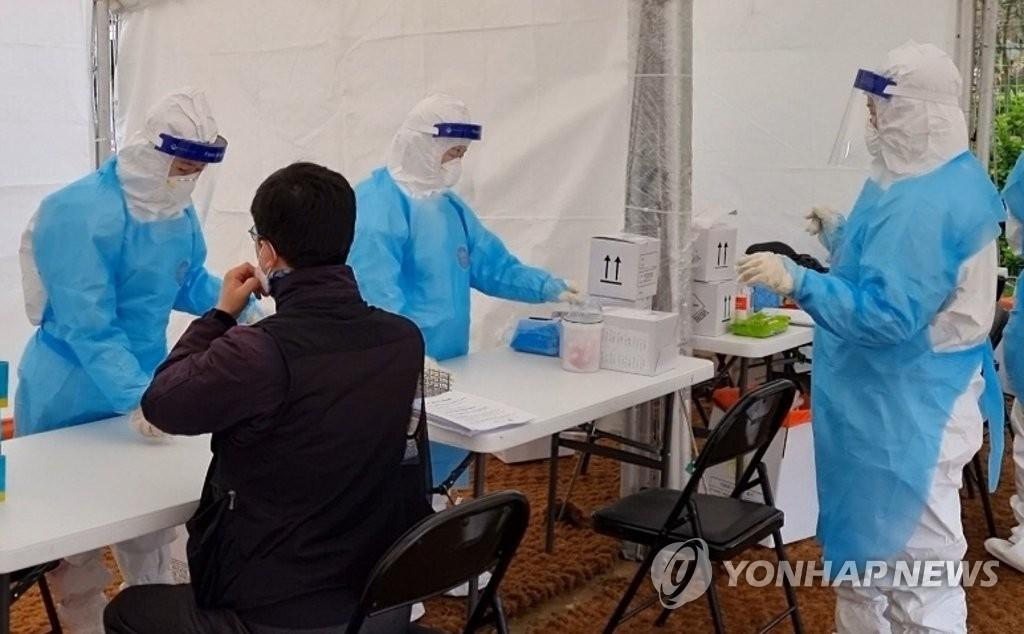 资料图片:市民在临时筛查诊所接受病毒检测。 韩联社
