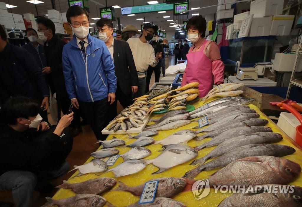 4月12日,在首尔市一处海鲜市场,韩国海水部长官文成赫(蓝衣)视察原产地管理现状。 韩联社