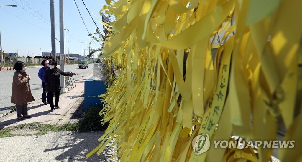"""资料图片:4月14日,在位于全罗南道木浦市的木浦新港,防波堤上挂满寄托哀思的黄丝带,悼念7年前因""""世越""""号客轮沉没遇难的人们。 韩联社"""