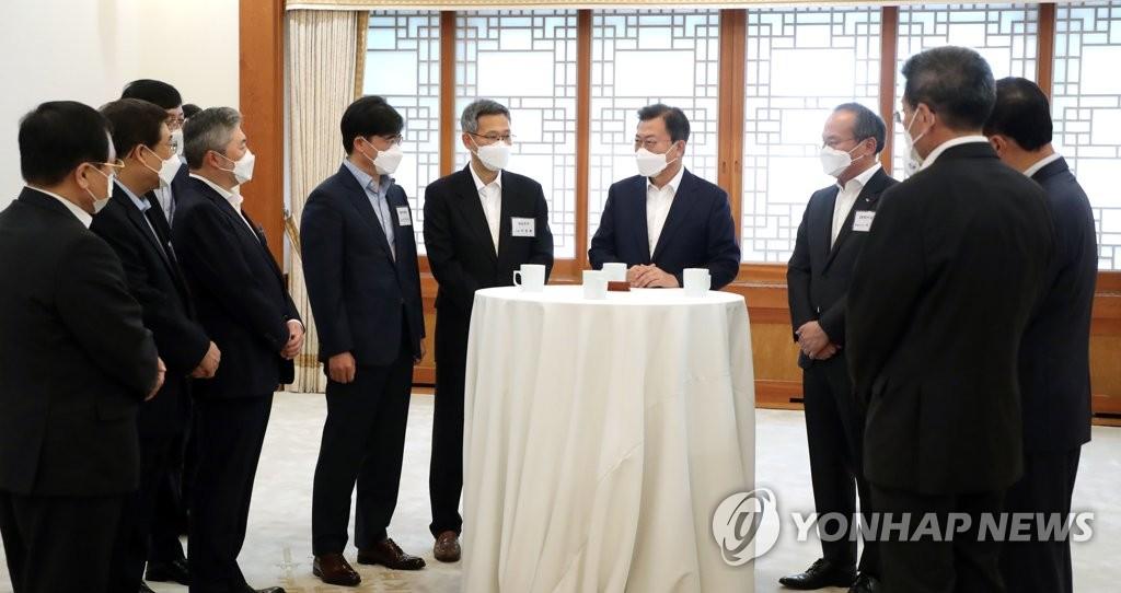 4月15日,在青瓦台,韩国总统文在寅(右四)在出席经济部长扩大会议之前同与会人员交谈。 韩联社