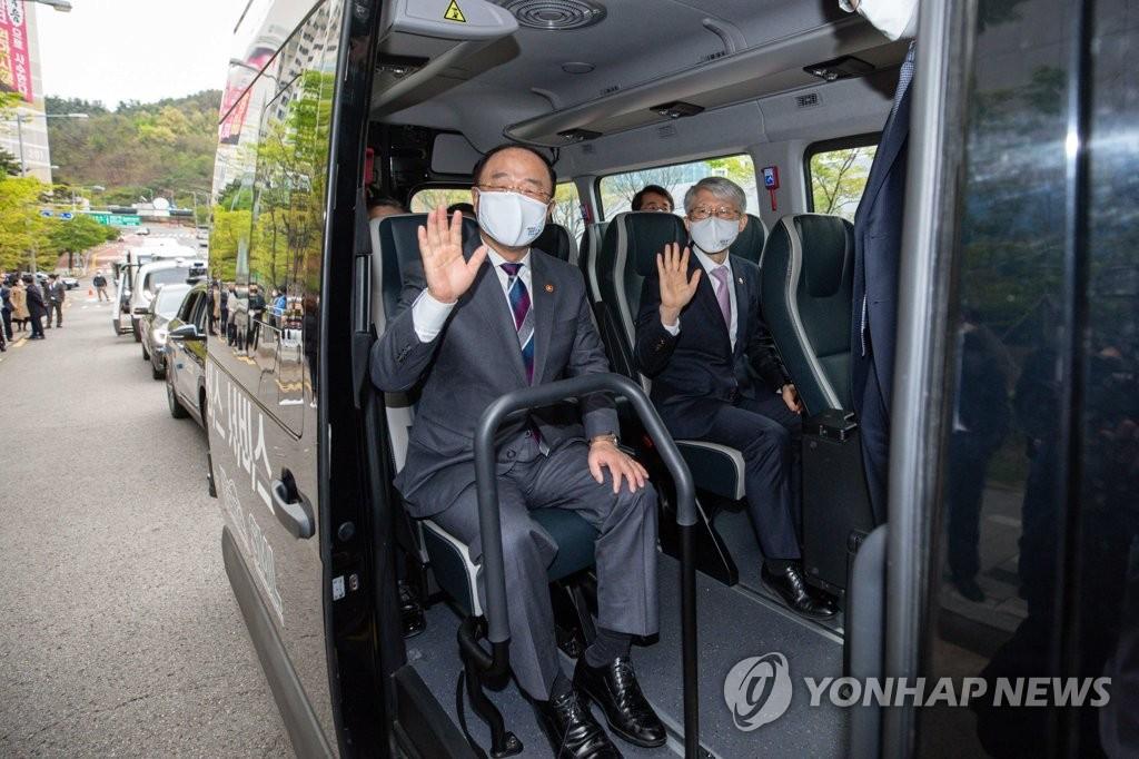 资料图片:4月16日,在位于首尔市麻浦区的未来移动出行中心,经济副总理兼企划财政部长官洪楠基(左)试乘无人驾驶汽车。 韩联社