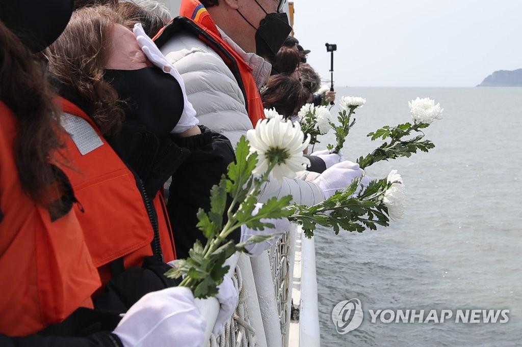"""4月16日,在全罗南道珍岛郡屏风岛附近""""世越""""号沉没海域,遇难者遗属等人向大海献花。 韩联社"""