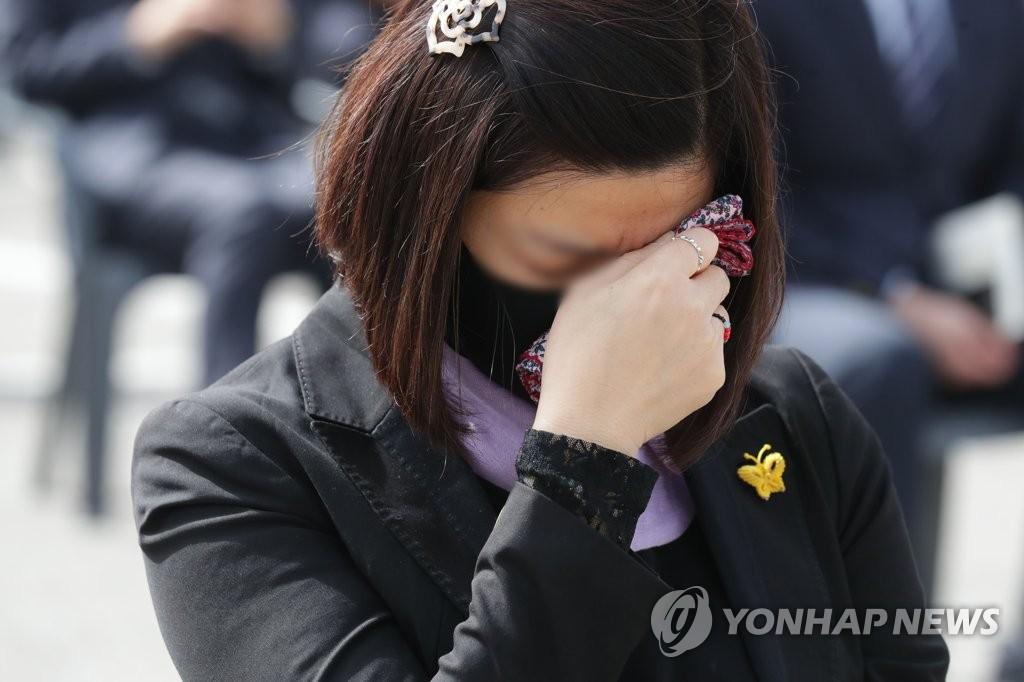 """4月16日,在京畿道安山市花郎游乐园,出席""""世越""""号沉船事故遇难者悼念仪式的市民忍不住流泪。 韩联社"""