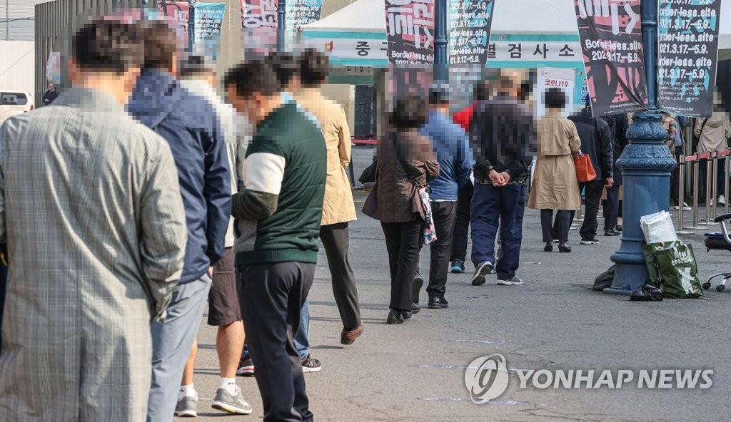 资料图片:市民排队候检。 韩联社