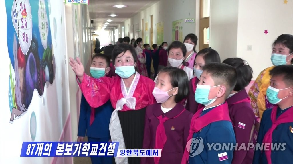 据朝鲜中央电视台26日报道,平安北道87所模范学校恢复正常上课。图为戴着口罩的小学生们在教室走廊听老师讲解。 韩联社/朝鲜央视(图片仅限韩国国内使用,严禁转载复制)