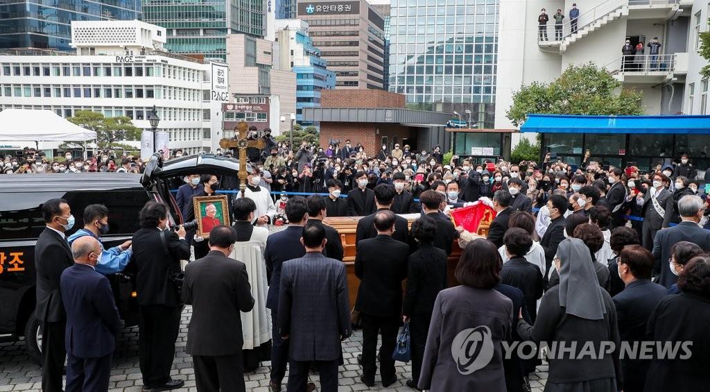 5月1日,天主教首尔大教区枢机主教郑镇奭的殡葬弥撒在首尔明洞教堂举行,图为信徒们目送灵柩上车。 韩联社