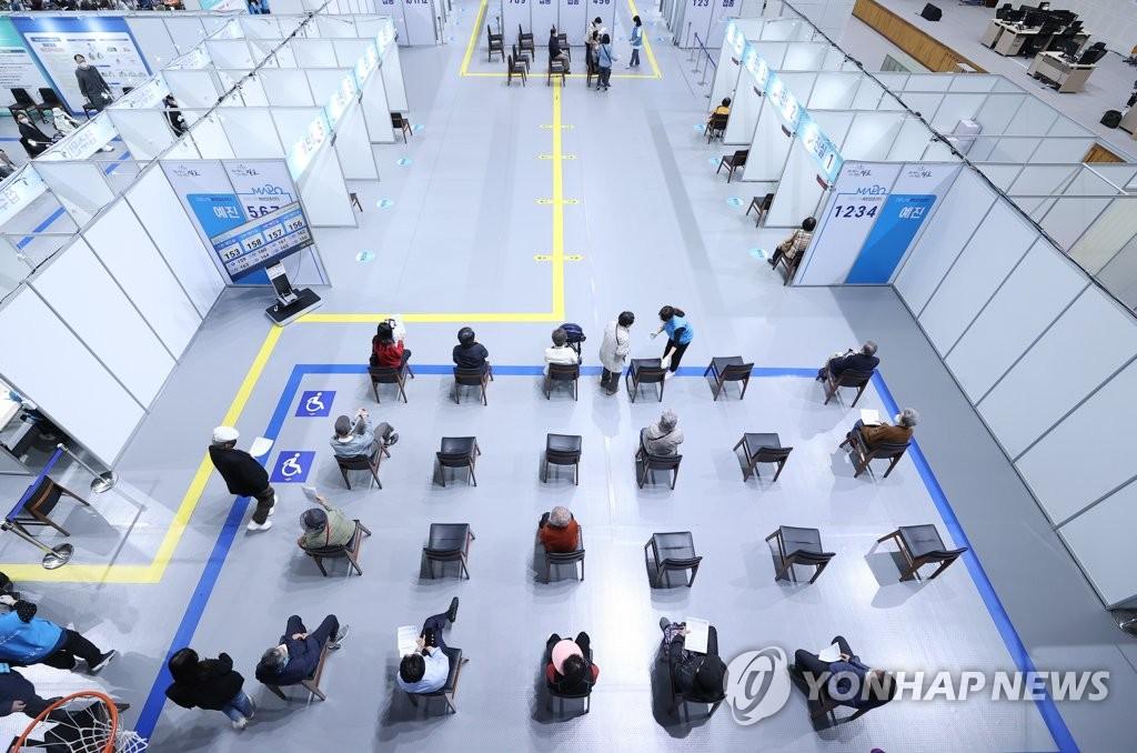 资料图片:市民等待接种疫苗。 韩联社