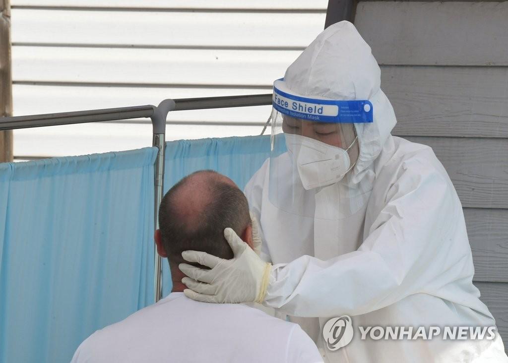 资料图片:5月3日,在设于江原道江陵市原长途巴士候车室的临时筛查诊所,一名外籍劳工接受新冠检测。 韩联社