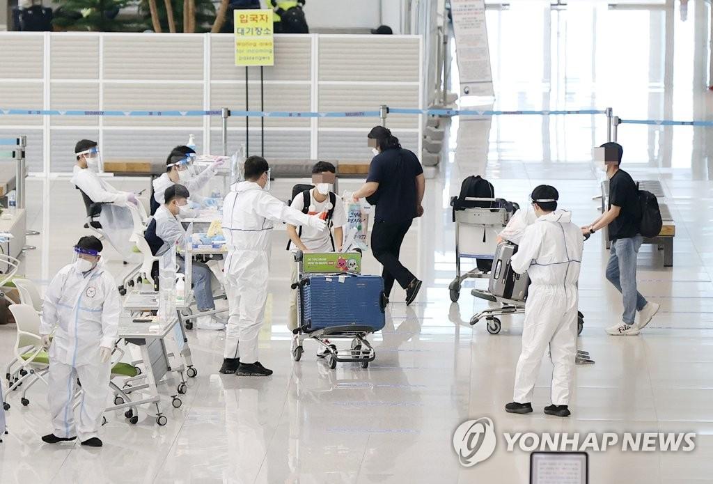 资料图片:5月5日,在仁川国际机场第二航站楼到达大厅,工作人员引导入境者入境。 韩联社