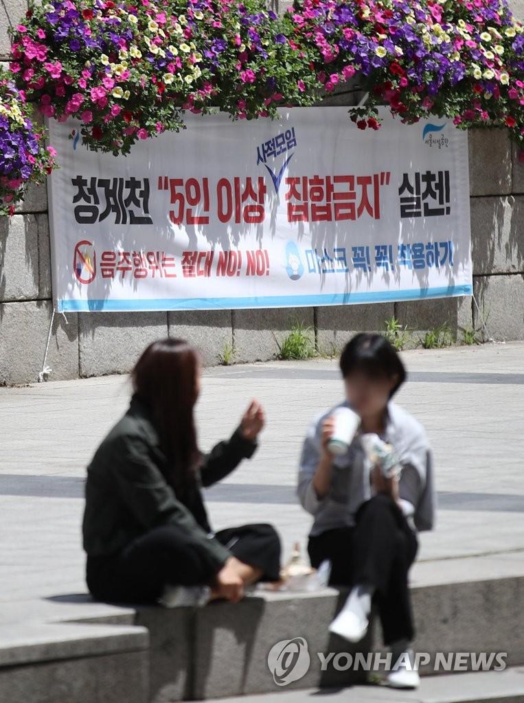 """资料图片:5月11日,在首尔清溪川,市民坐在""""禁止5人以上聚集""""标语前休息。 韩联社"""