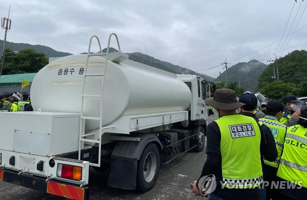 5月18日上午,在庆尚北道星州郡草田面(乡)韶成里,载着饮用水的运输车辆驶入萨德基地。 韩联社