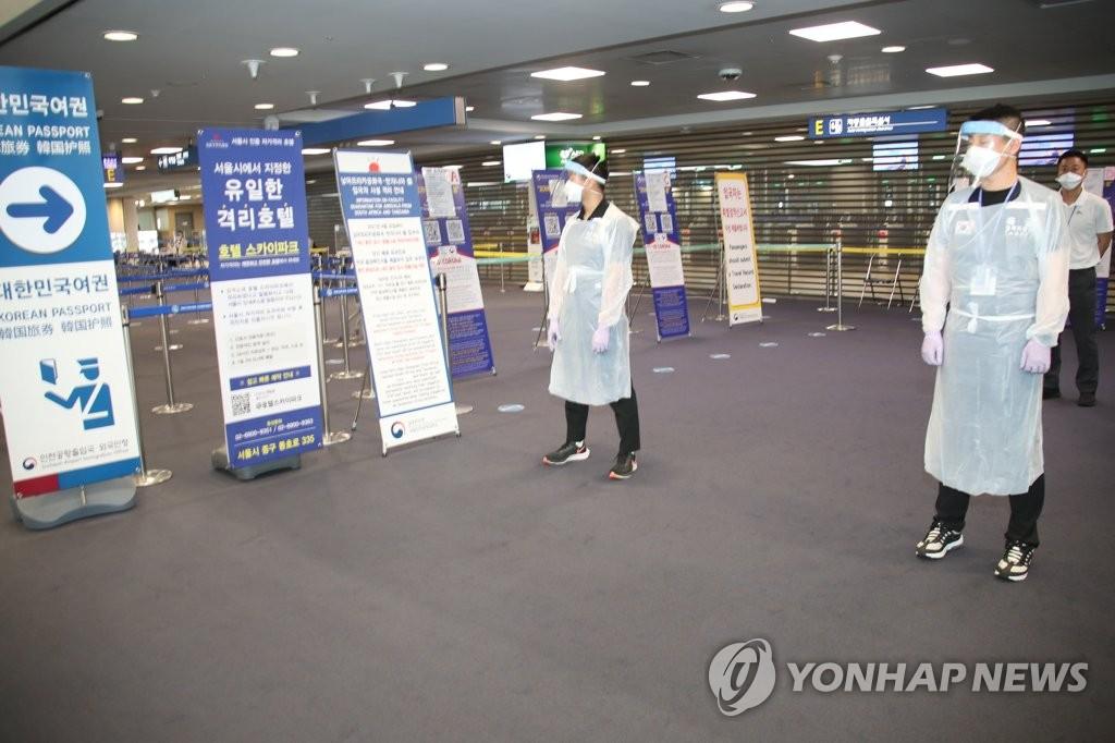 资料图片:6月24日,在仁川国际机场入境处,防疫人员严阵以待。 韩联社