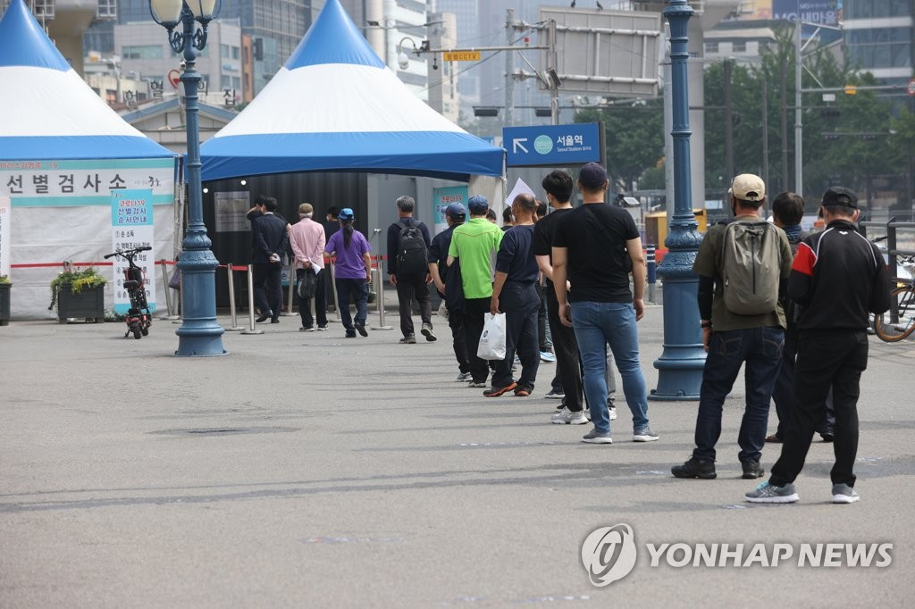 资料图片:6月6日,在首尔火车站的临时筛查诊所,市民们排队候检。 韩联社