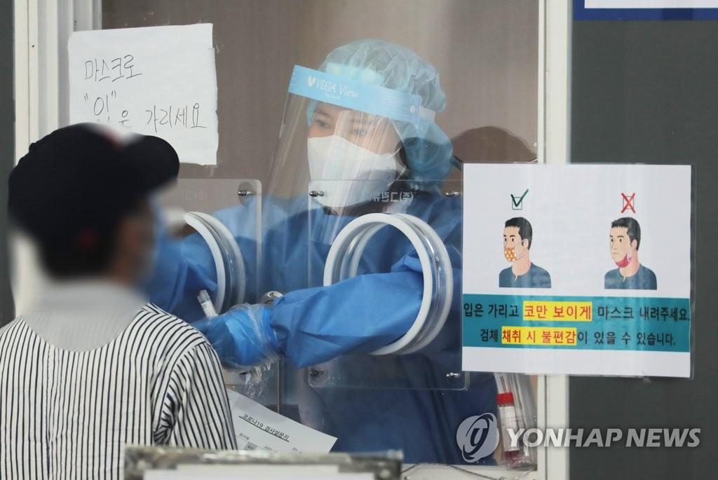资料图片:6月7日,在首尔火车站的临时筛查诊所,医务人员正为市民进行新冠病毒检测。 韩联社