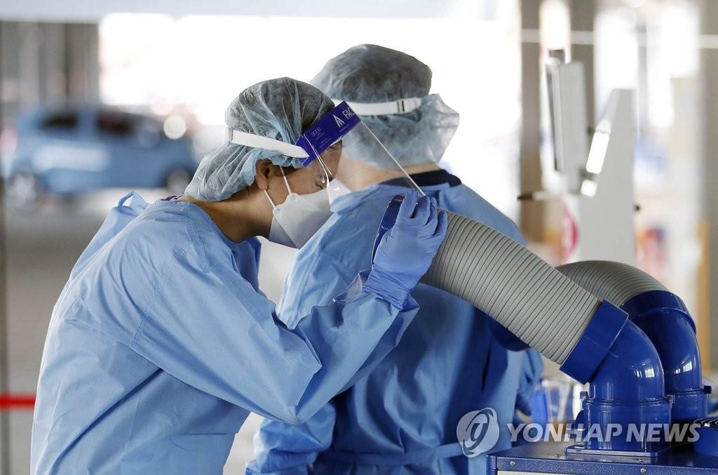 资料图片:6月9日,在光州北区的一处卫生站,医务人员吹冷风消暑。 韩联社/光州北区政府供图(图片严禁转载复制)