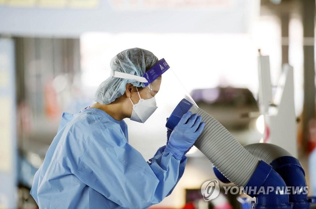 资料图片:吹冷气降温的医务人员 韩联社
