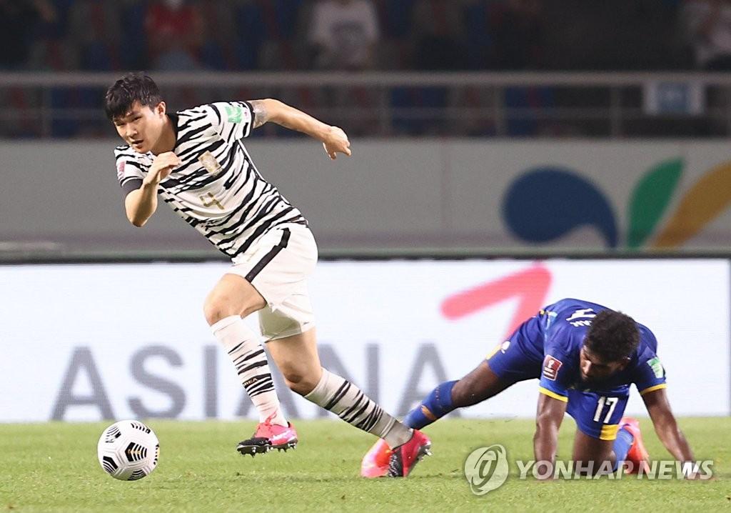 资料图片:韩国男足运动员金玟哉(左) 韩联社