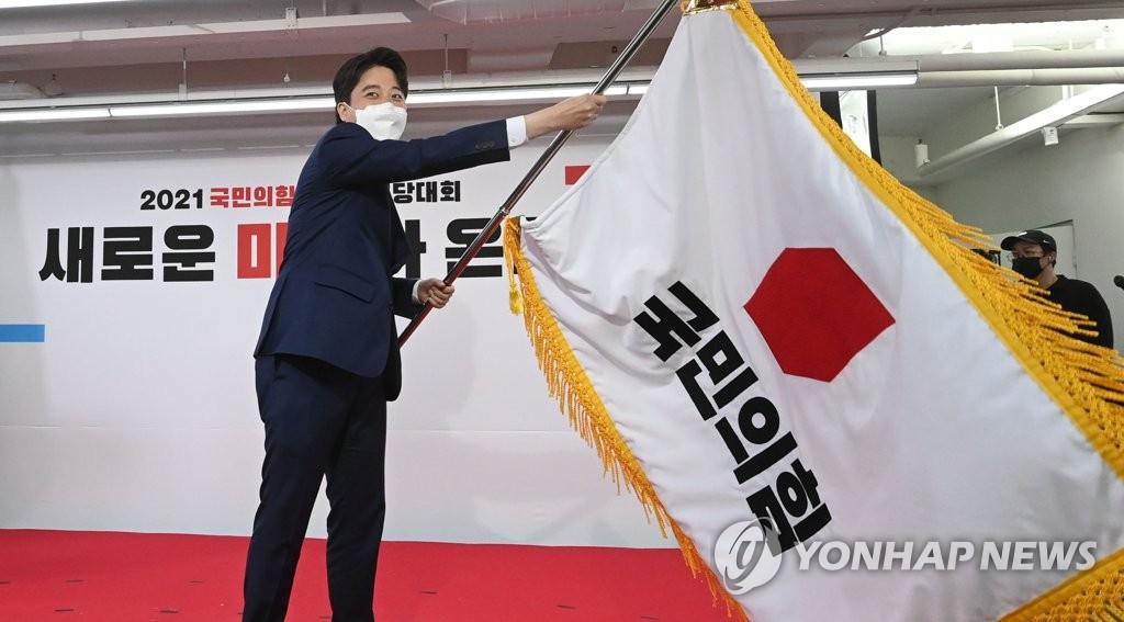 6月11日,在国民力量党全党大会上,新任党首李俊锡挥舞党旗。 韩联社