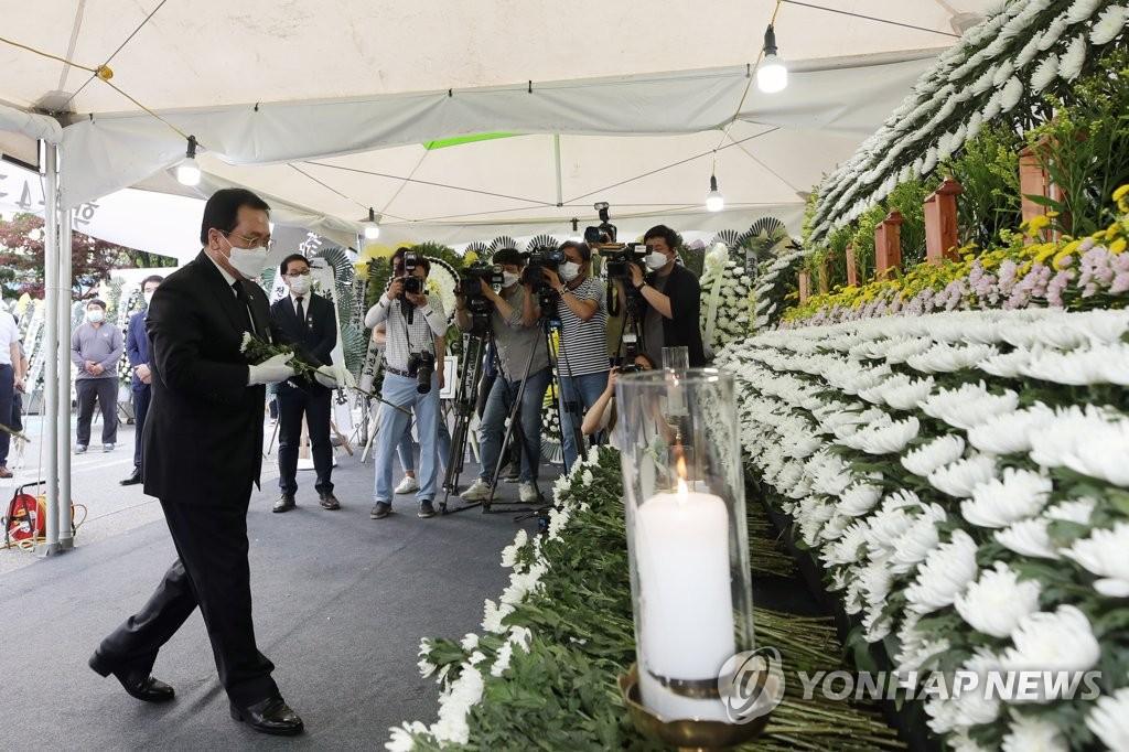 6月11日下午,在光州市东区区政厅停车场,俞英民向拆楼倒塌事故遇难者灵前献花。 韩联社