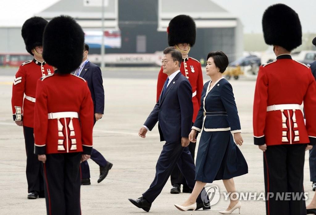 当地时间6月11日下午,韩国总统文在寅(左)和夫人金正淑搭乘空军一号专机抵达英国康沃尔纽基机场。文在寅此行将出席七国集团峰会。 韩联社