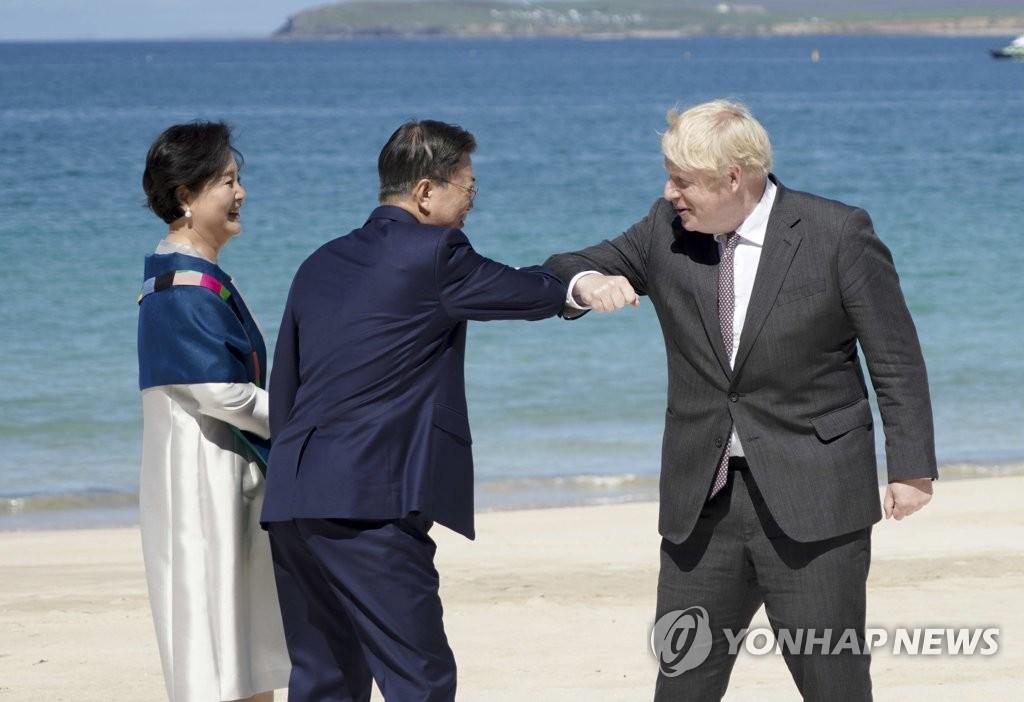 资料图片:当地时间6月12日,在英国康沃尔卡比斯贝,总统文在寅(左二)与夫人金正淑(左一)出席七国集团(G7)峰会受邀国欢迎仪式。图为文在寅(中)与英国首相约翰逊(右)碰肘致意。 韩联社