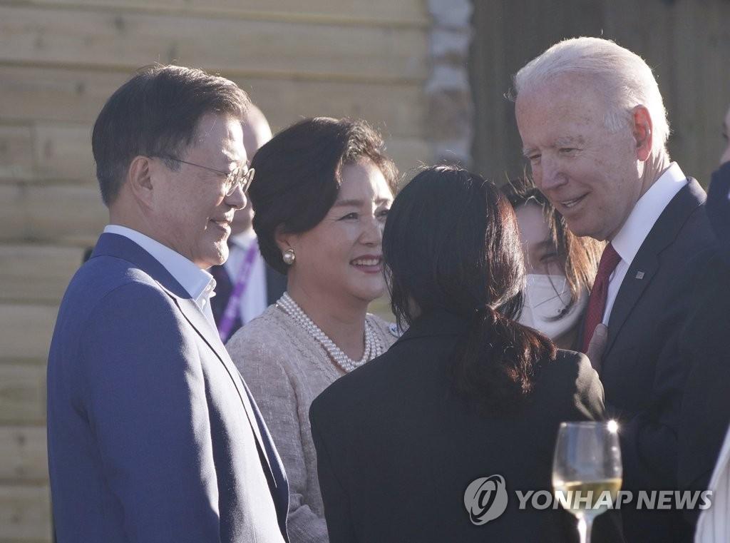 资料图片:当地时间6月12日,在英国康沃尔,韩国总统文在寅(左)伉俪同美国总统拜登交谈。 韩联社