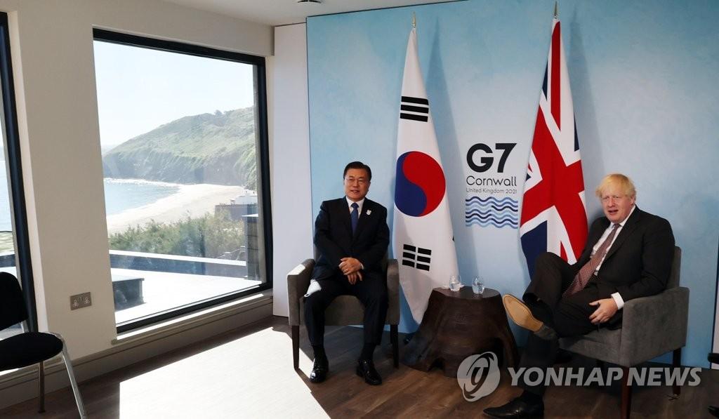 当地时间6月13日,在英国康沃尔卡比斯贝,韩国总统文在寅(右)同英国首相鲍里斯·约翰逊举行会谈。 韩联社
