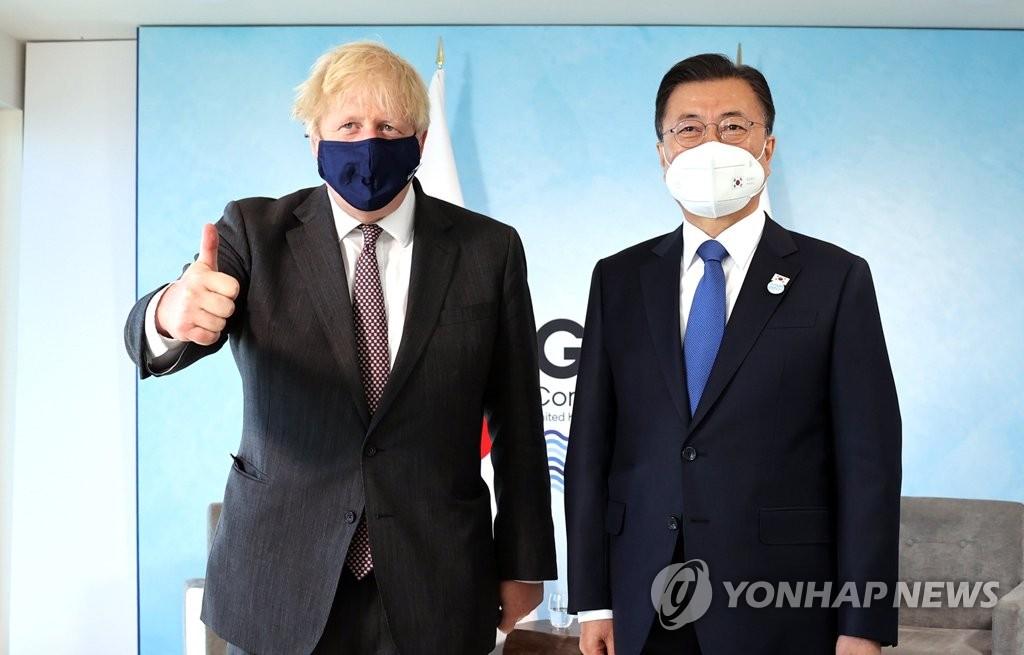 当地时间6月13日,在英国康沃尔卡比斯贝,韩国总统文在寅(右)同英国首相鲍里斯·约翰逊举行会谈。图为两位领导人合影留念。 韩联社
