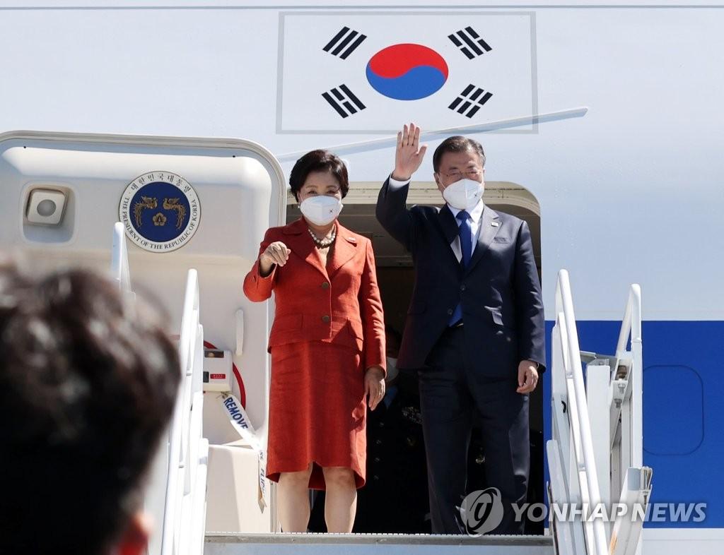 当地时间6月13日,在英国康沃尔纽基机场,韩国总统文在寅(右)与夫人金正淑启程前向送行人群挥手致意。 韩联社
