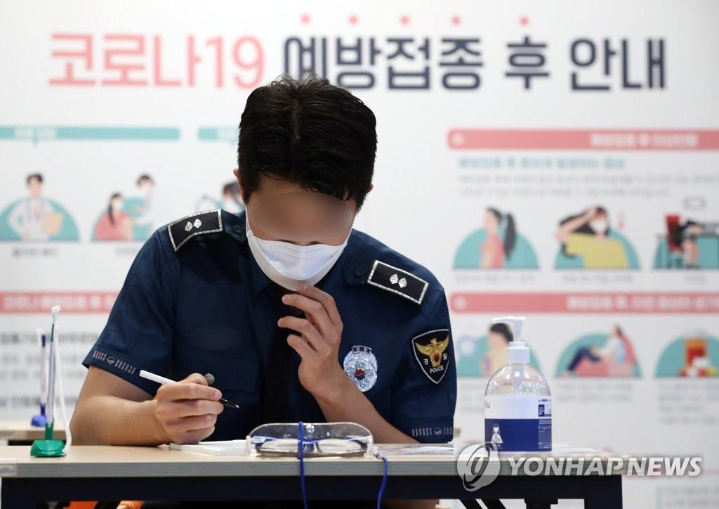 资料图片:一名警察在接种疫苗前填写问诊表。 韩联社