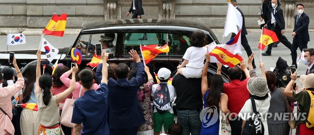当地时间6月15日,在西班牙首都马德里,当地韩侨向韩国总统文在寅乘坐的车辆挥动太极旗表示欢迎。 韩联社