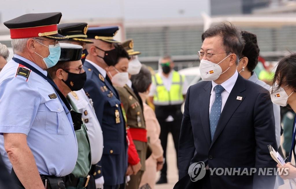 当地时间6月17日,在西班牙巴塞罗那安普拉特机场,韩国总统文在寅(右)启程回国前同前来欢迎的人群致意。 韩联社