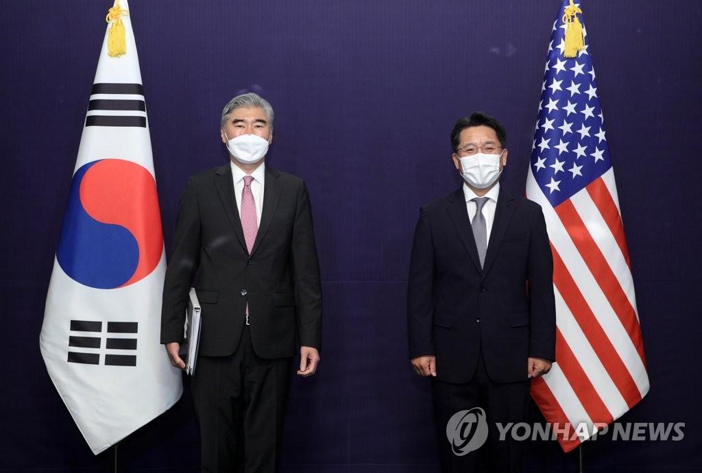 6月21日,在首尔市中区的乐天酒店,韩国外交部韩半岛和平交涉本部长鲁圭悳(右)和美国对朝特别代表星·金在进行韩美两国朝核磋商前合影。 韩联社