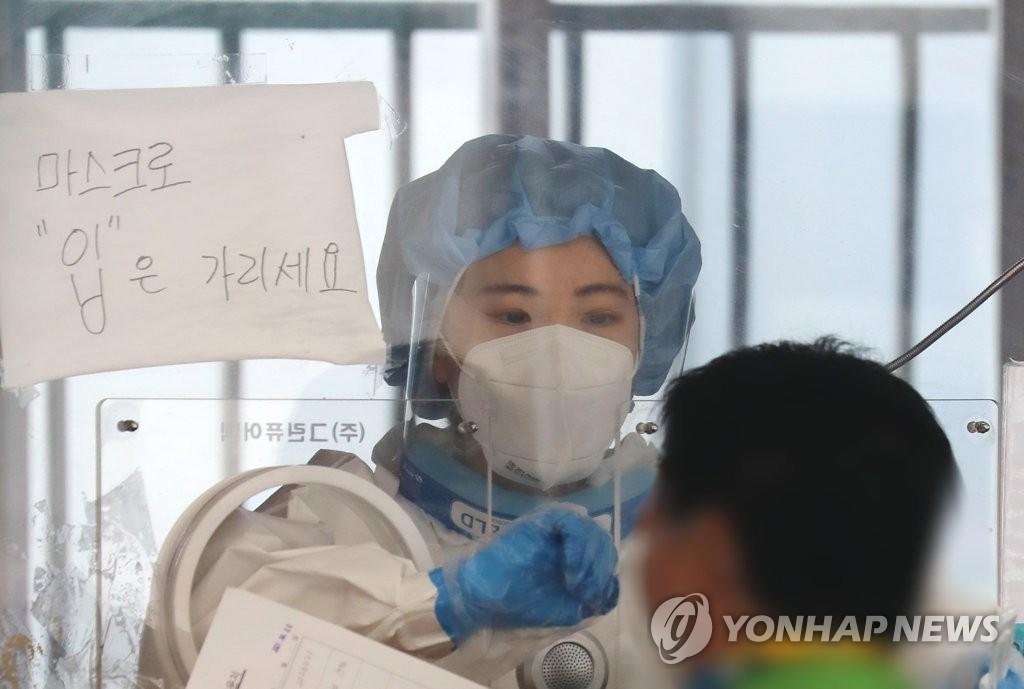 资料图片:在一处筛查诊所,医务人员进行新冠病毒检测。 韩联社