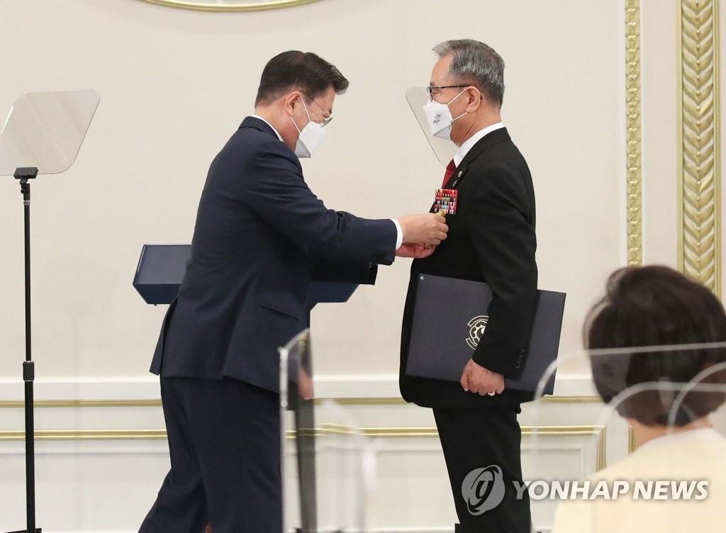 6月24日,在青瓦台举行的国家有功人员及家属午宴上,总统文在寅(左)向参加越南战争的有功人员授予国民表彰。 韩联社