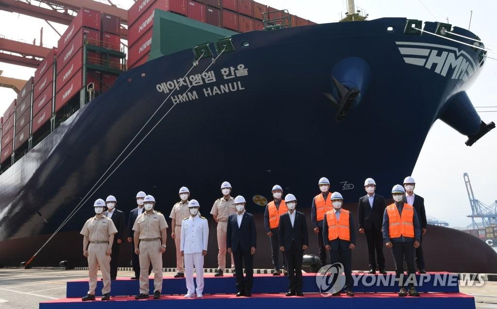 6月29日,在釜山新港,韩国总统文在寅出席韩国航运公司HMM(原现代商船)第20艘1.6万标箱(TEU)级集装箱船启航仪式。图为文在寅与船员及码头工人合影。 韩联社