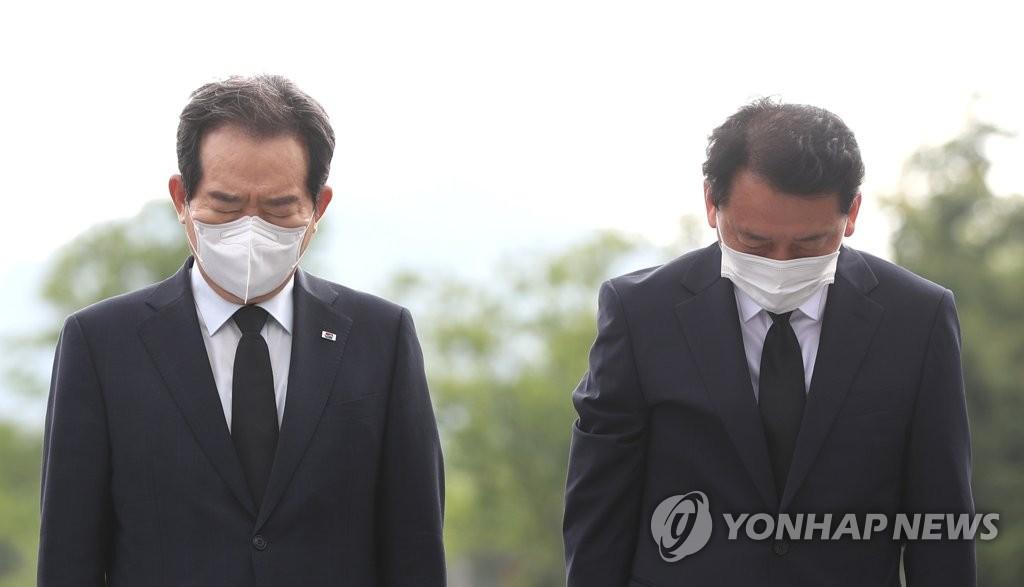 资料图片:李光宰(右)和丁世均参拜前总统卢武铉墓碑。 韩联社