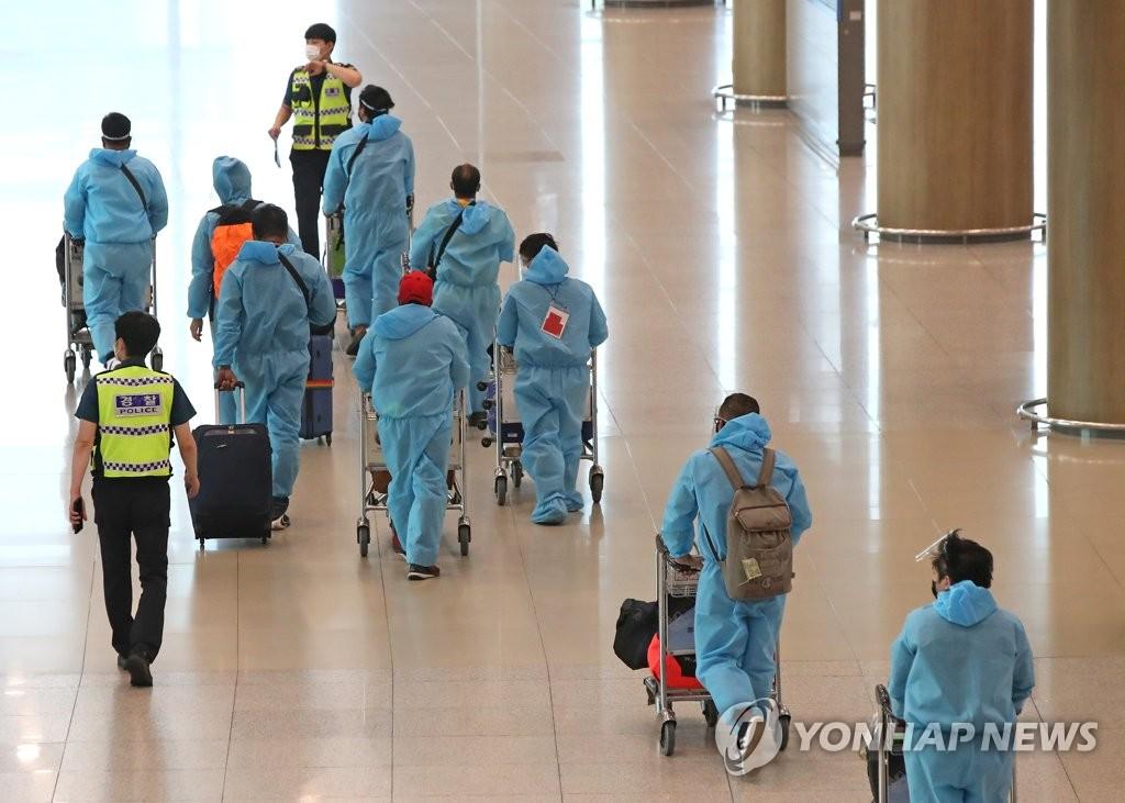 资料图片:7月2日,在仁川国际机场第一航站楼,自印度入境的旅客在警察的引导下前往检疫点。 韩联社