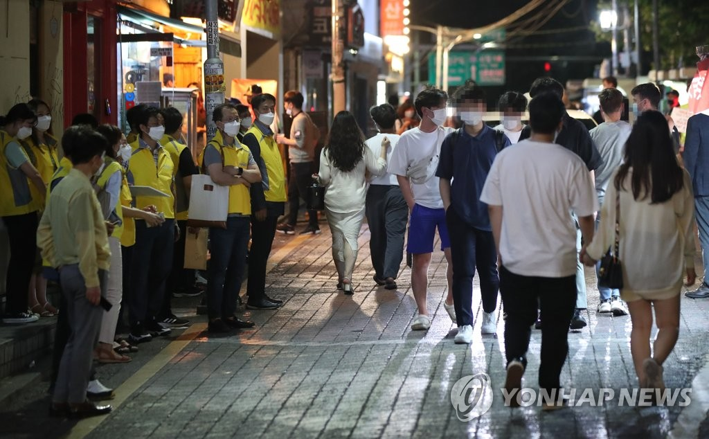 资料图片:7月2日晚,首尔市麻浦区政府及地区居民等正在街头宣传保持社交距离和呼吁民众佩戴口罩。 韩联社