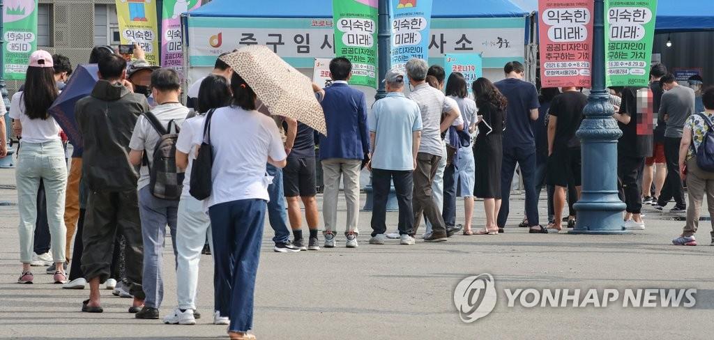 资料图片:排队接受新冠病毒检测的市民 韩联社