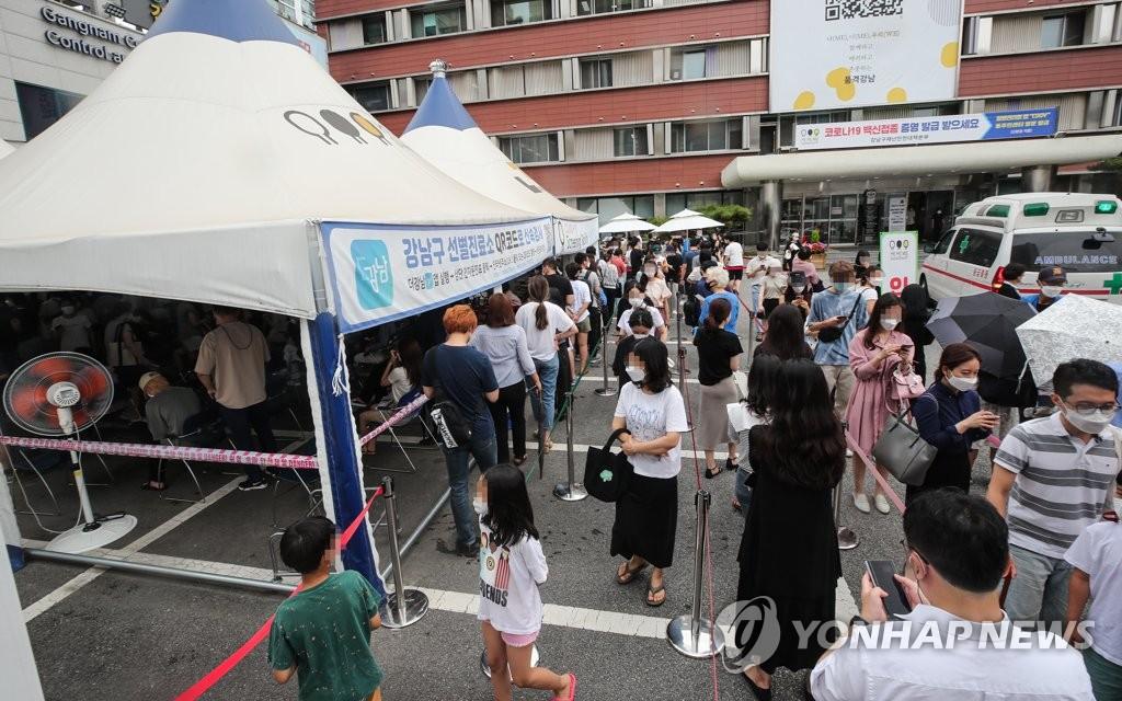 资料图片:7月7日下午,在首尔市江南区卫生站的核酸检测点,市民冒着酷暑排队候检。 韩联社