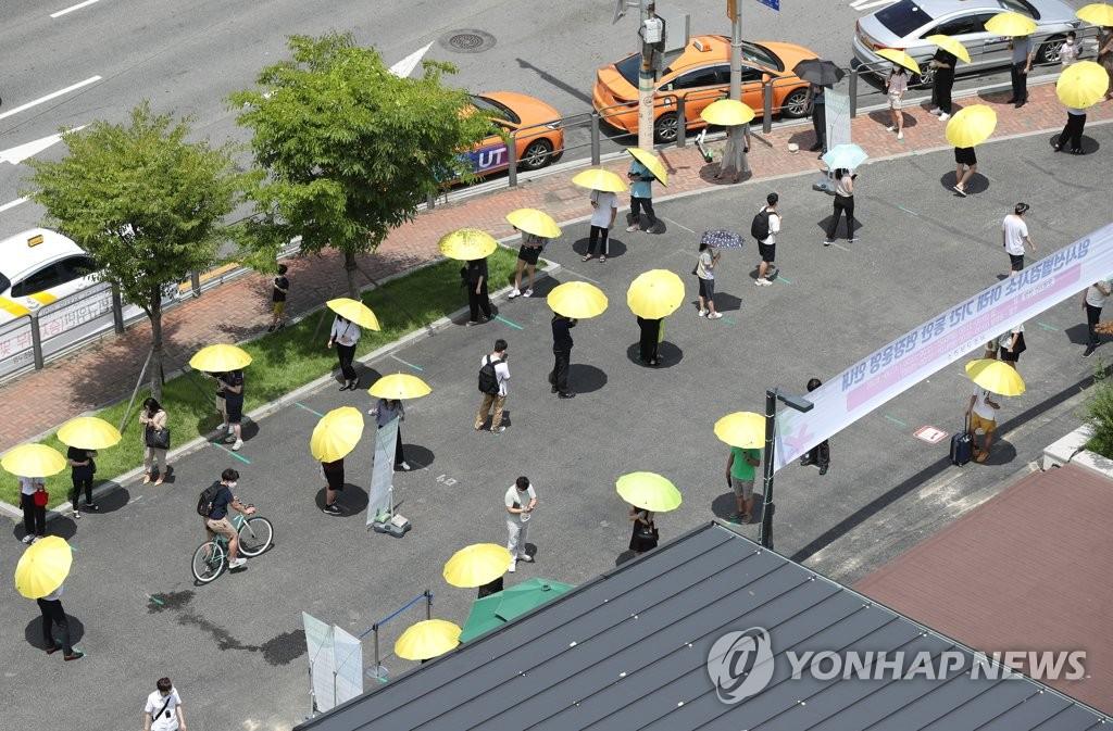 资料图片:排队待检的市民 韩联社
