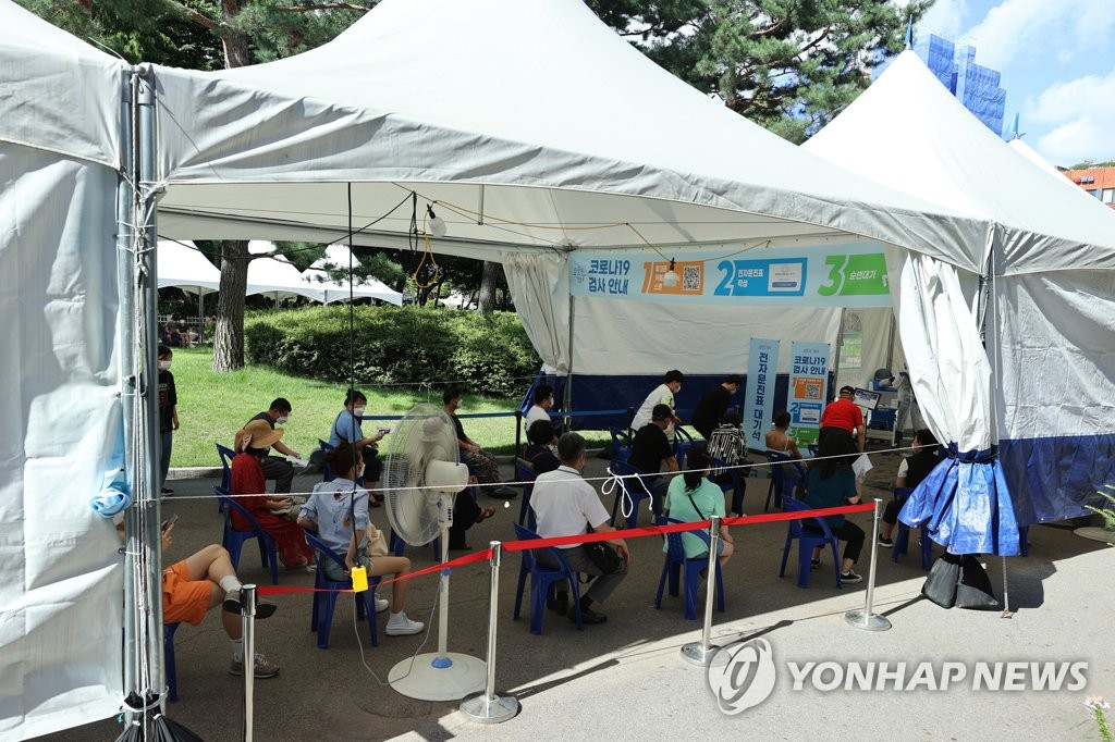 资料图片:7月15日,在首尔永登浦区卫生站的筛查诊所,市民排队待检。 韩联社