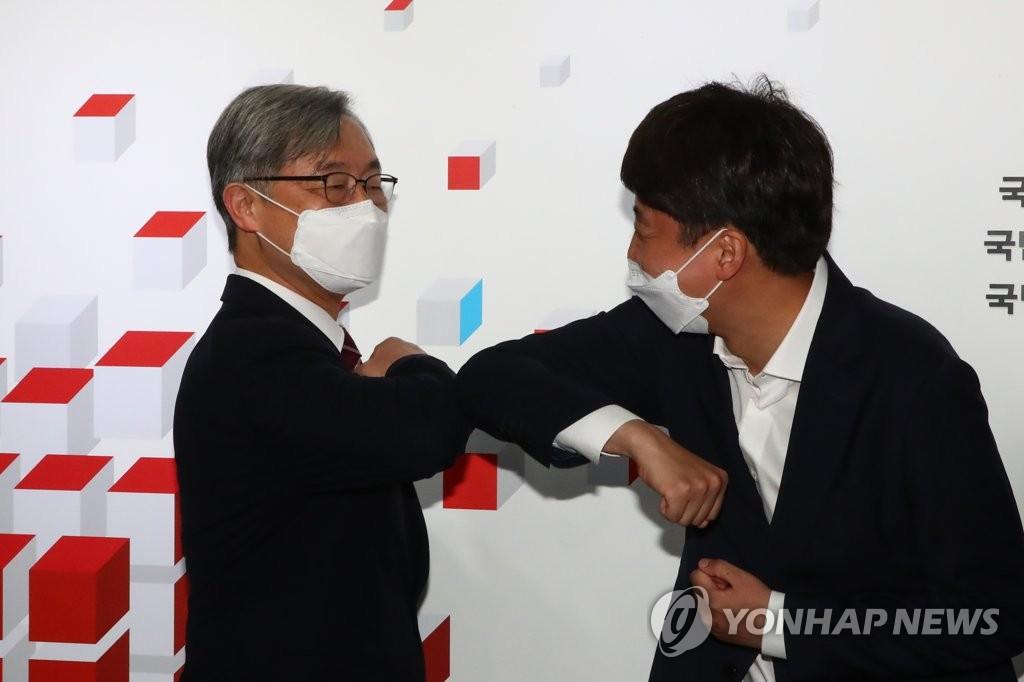 7月15日,在位于汝矣岛的国民力量党办公楼,李俊锡(右)和崔在亨碰肘致意。 韩联社