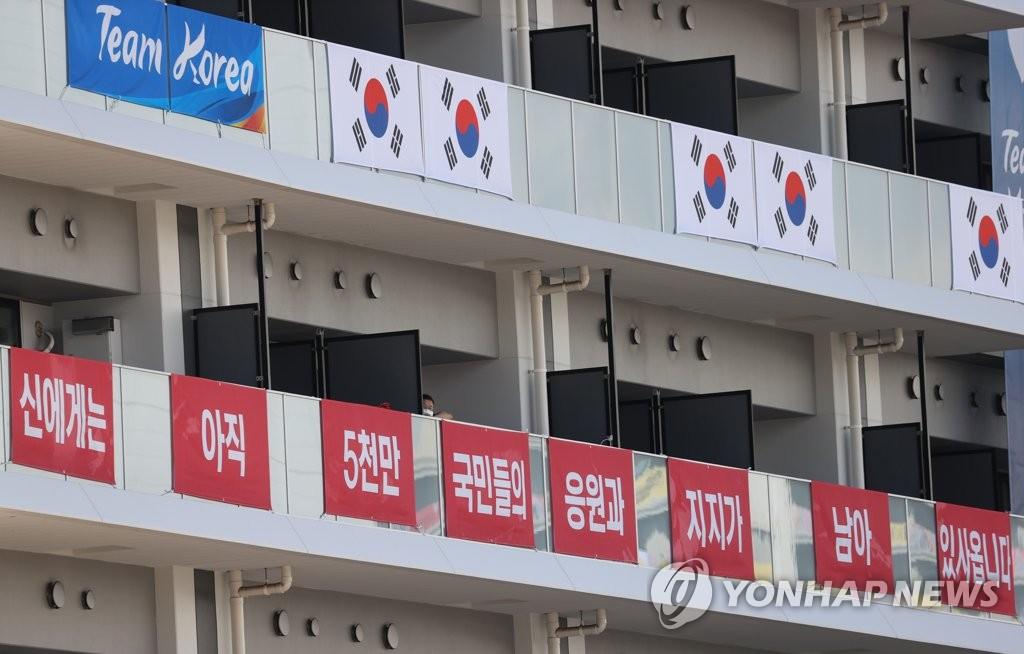 资料图片:韩国奥运军团在选手村宿舍阳台挂起条幅和国旗。 韩联社