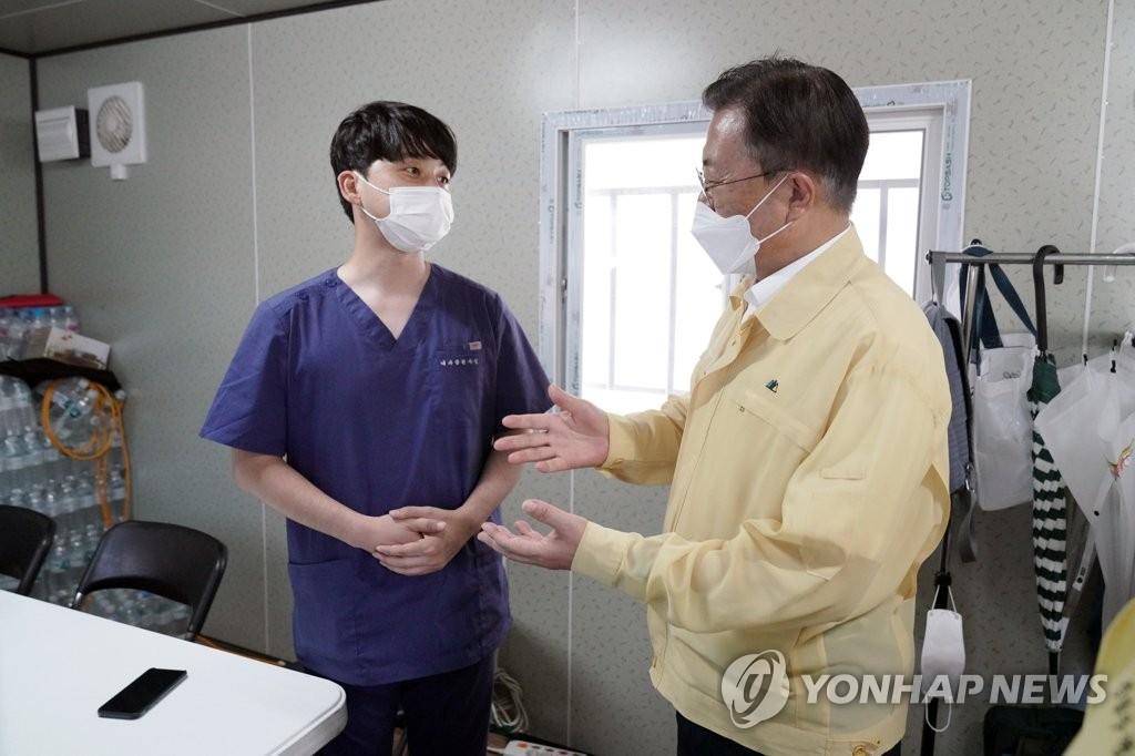 7月18日上午,在三成站附近的检测点,文在寅(右)和医务人员交谈。 韩联社/青瓦台供图(图片严禁转载复制)